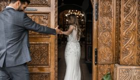 Groom and bride holding hands and entering in church, back view